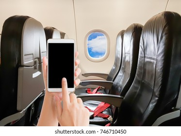 woman use mobile phone in the cabin with empty seat and blue sky view at the window