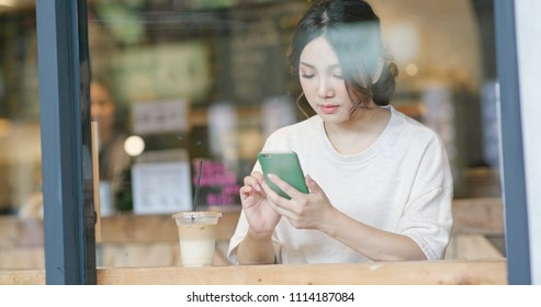 Woman use of mobile phone in cafe