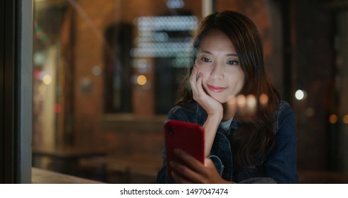 Woman use of mobile phone in coffee shop inside coffee shop, window glass reflection