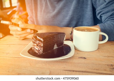 woman use mobile phone with coffee cup and chocolate cake on wood table in coffee shop.