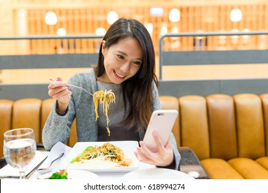Woman use of mobile phone and eating together