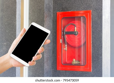 woman use mobile phone with the fire hose rack on the wall