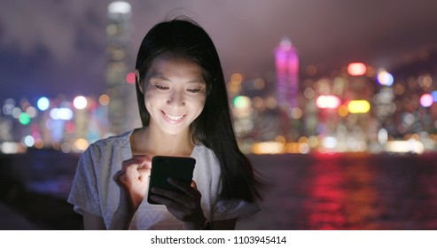 Woman use of mobile phone in Hong Kong at night