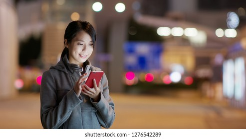 Woman use of mobile phone for searching location in the street at night
