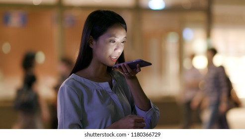 Woman use of mobile phone sending audio message at night