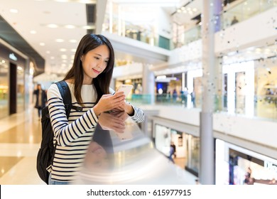 Woman use of mobile phone in shopping center