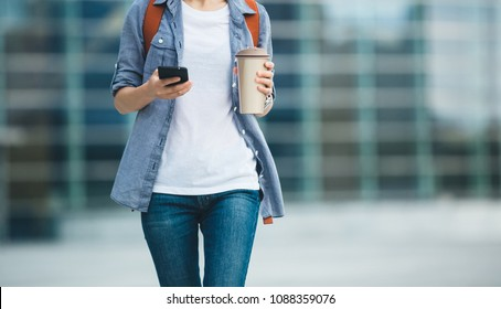 Woman use mobile phone walking with coffee thermo cup in hand