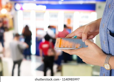Woman use mobile phone,blur image at front of ATM as background.