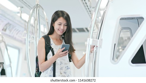 Woman use of smart phone on train compartment