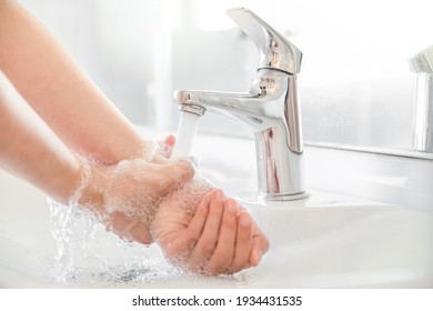 Woman use soap and washing hands rubbing with soap under the water tap. Hygiene new normal concept to stop spreading coronavirus or influenza virus in hospital or public wash room.