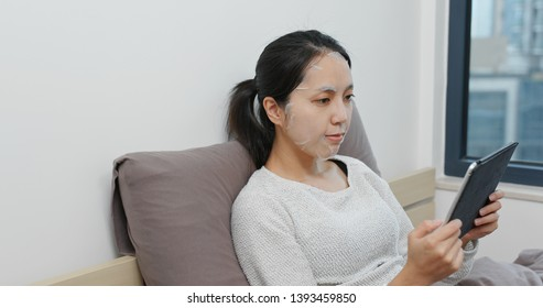 Woman use of tablet computer with apply face mask on bed