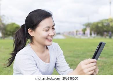 Woman use tablet in park
