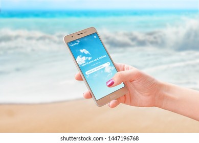 Woman use travel app on smart phone to find next travel destination. Beach and sea in background. Close-up.