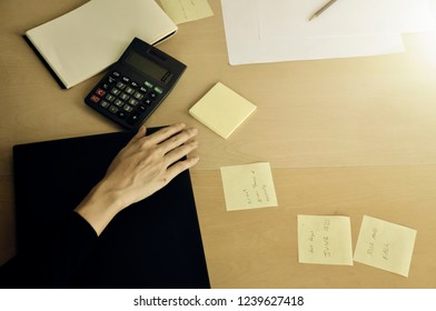 Woman useing note or write memory. Hand of woman Worker on Desk with notesl and calculator. Vintage tone