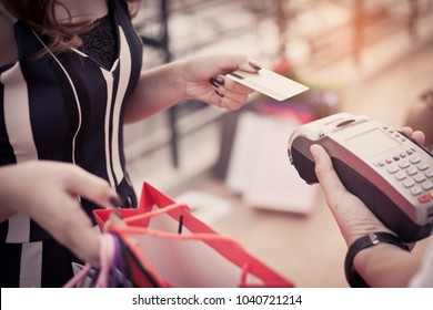 A woman uses a credit card to pay for goods with a cashier. Shopping concept.
