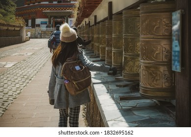 Woman uses Golden Prayer wheels at Shika Snow Mountain is regarded as a holy mountain for the local Tibetans West at the Shangri-La county, Yunnan
