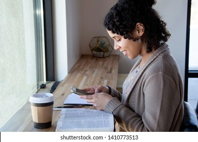 woman uses her phone while studying her bible