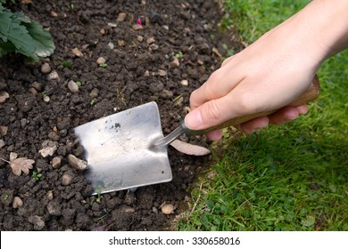 Woman uses a metal hand trowel to dig in the soil of her garden flower bed