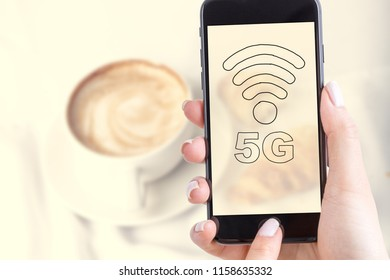 Woman uses mobile technology 5g or Lte. Coffee on the table in the background.