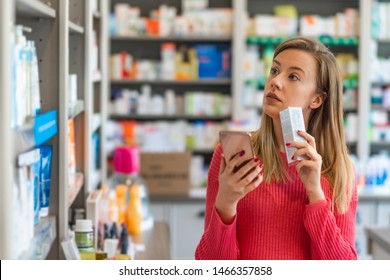 Woman uses smart phone while in pharmacy. They have the best medicine here. They have so much on offer here. Woman Checking Supplement On Smartphone At Pharmacy