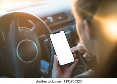 Woman uses a smartphone while driving at the wheel.