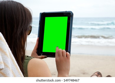A woman uses a tablet device while on the beach, symbolizing the ability to blend work and rest while working from anywhere.