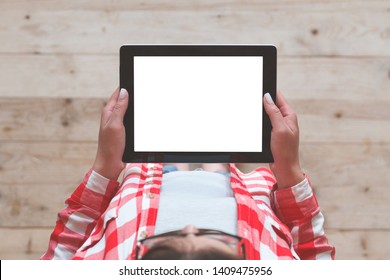 A woman uses a tablet, holding in the hands against the background of a wooden plank floor. Top view
