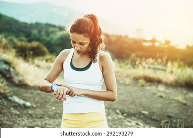Woman using activity tracker or heart rate monitor. Outdoor fitness concept. Toned image