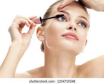 Woman using black mascara on eyelashes isolated on white background. Beauty concept