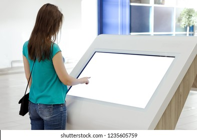 Woman is using a blank touch screen of interactive information stand in the supermarket.