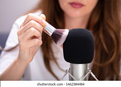 Woman using brush on microphone to make ASMR sounds