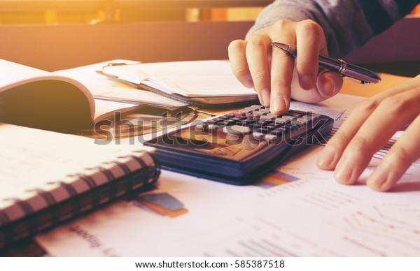 Femme utilisant une calculatrice avec faisant de la finance au bureau à la maison.