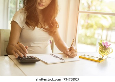 A woman using the calculator and her make note calculate about cost at home.