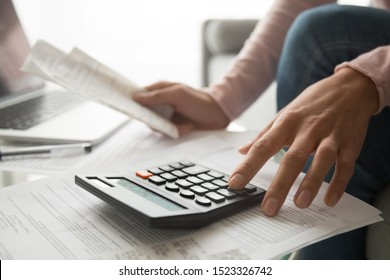 Woman using calculator holding paper bills calculating planning expenses money payments concept, female hands counting data vat taxes cost doing paperwork at home office table, close up view