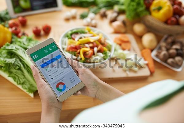Žena používající kalorie počítadlo aplikace na svém smartphonu