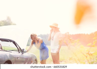 Woman using cell phone while friend examining broken down car
