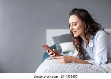 Woman using cellphone bed at home. Communication by phone.