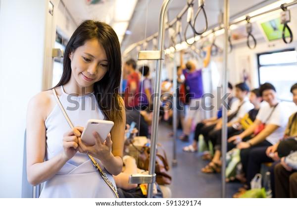 車内で携帯電話を使う女性