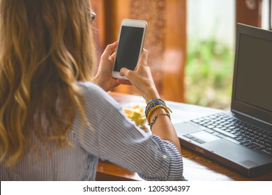 Woman using cellphone and laptop inside house while having a breakfast.