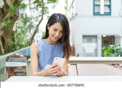 Woman using cellphone in outdoor cafe