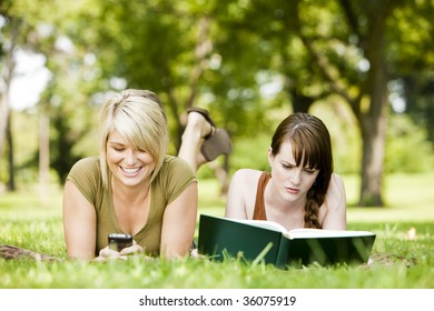 Woman using cellphone while her friend reads a book