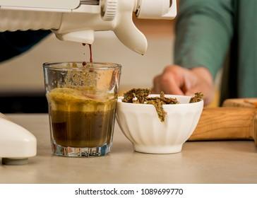 Woman using a centrifuge machine to prepare a detox juice.