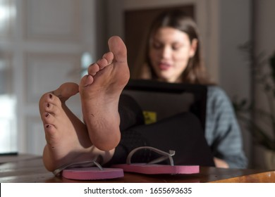 Woman using computer with her feet on the desk
