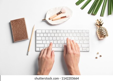 Woman using computer keyboard on white table decorated with tropical leaf, top view. Creative design ideas