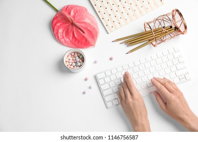 Woman using computer keyboard on white table decorated with tropical flower, top view. Creative design ideas