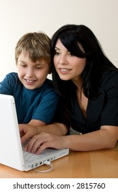 A woman using a computer while a child happily, looks on.