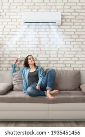 Woman Using Conditioner In Room. Living Room Cooling