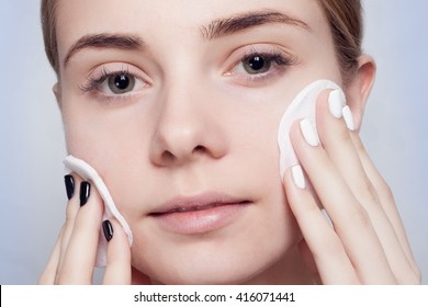 Woman using cotton pad. Happy smiling beautiful young woman cleaning skin by cotton pad. light background. Beautiful Spa Woman Smiling. Perfect Fresh Skin. Youth and Skin Care Concept