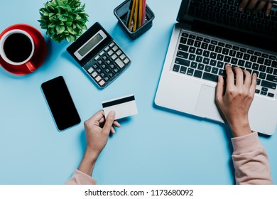 Woman using credit card with mobile phone and laptop and coffee cup on office desk.Online payment Concept.
