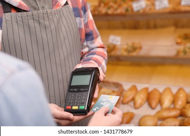 Woman using credit card for terminal payment in bakery, closeup. Space for text